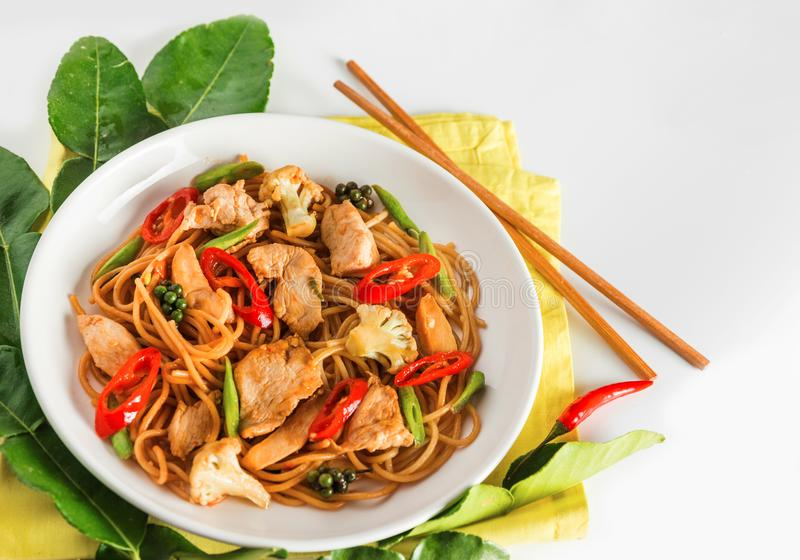 Traditional spicy asian cuisine food: wok stir fry spaghetti with fried chicken. And thai spices and herbs stock images