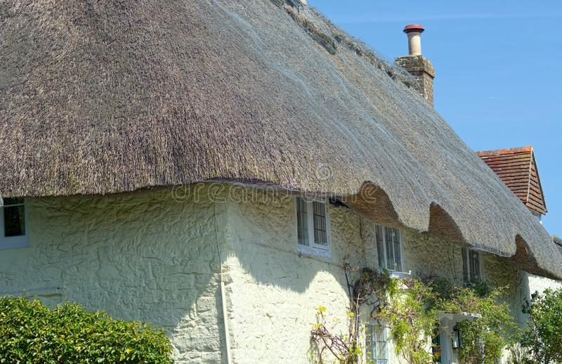 Traditional stone cottage with reed thatched roof stock photo