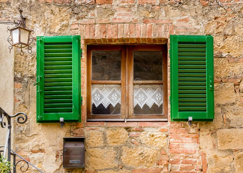Traditional Tuscan home with green shutters stock images