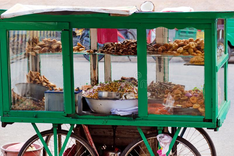 Traditional street food of Sri Lanka - chickpea with coconut, small fried fish, vegetable patties, donuts on a mobile cart. royalty free stock images