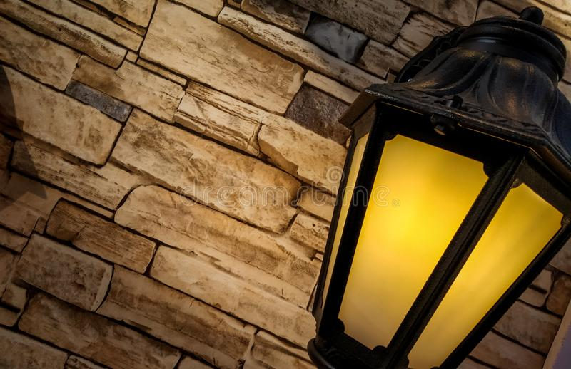 Traditional street light placed on a stone tiles background. With yellow gradient light in it royalty free stock photo