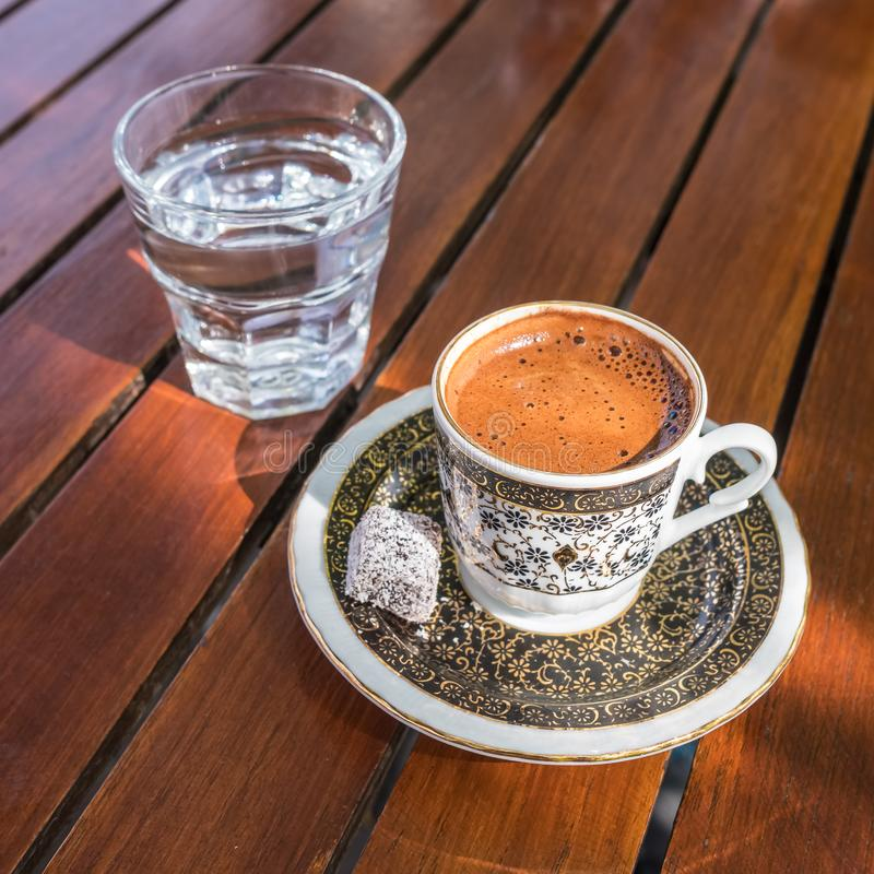 Traditional strong and dark Turkish coffee served with a glass of water on a side on a wooden table in  outdoor cafe. Turkey royalty free stock photos