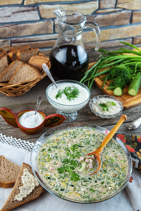 Traditional summer cold soup okroshka with kvass. Traditional Russian cold soup okroshka. Sour cream, horseradish, salt, bread and herbs on background stock photos