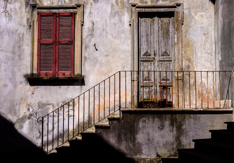 Traditional sun-lit rustic Italian architecture facade with stairs alongside iron railing leading to worn out stairs and wooden do stock photography