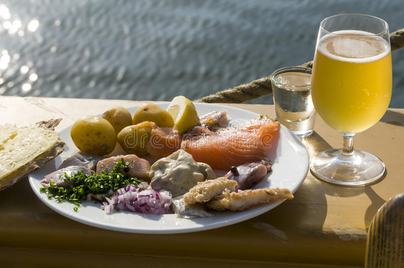 Traditional Swedish midsummer dish with pickled herring. Fried Baltic herring, smoked salmon, new potatoes served with hardbread and hard cheese. To drink beer stock image