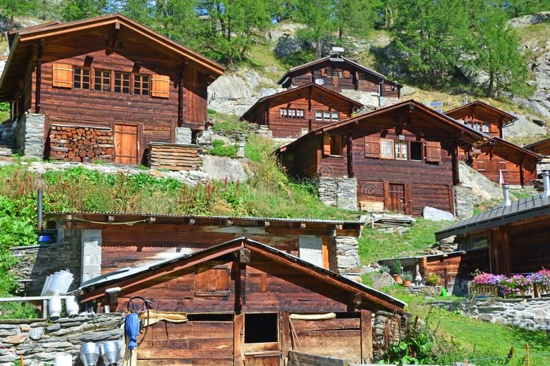 Traditional Swiss Mountain Chalets. In a mountain summer hamlet with small farm in the foreground stock photo