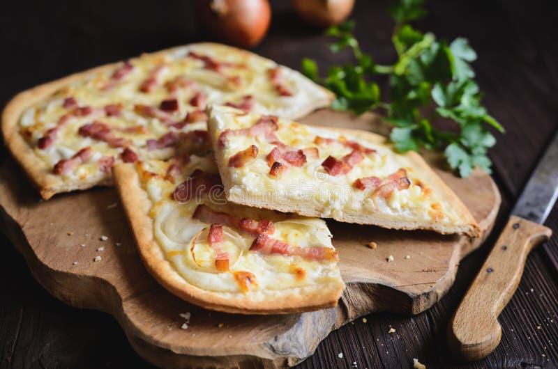 Traditional Tarte flambée with crème fraiche, cheese, onion and bacon. Slices stock photos