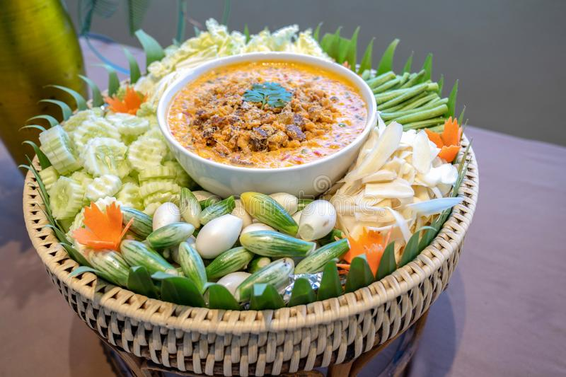 Traditional Thai chilli spicy sauce called Nam Prik in white bowl in the middle of vegetable cabbage cucumber carrot eggplant stock image