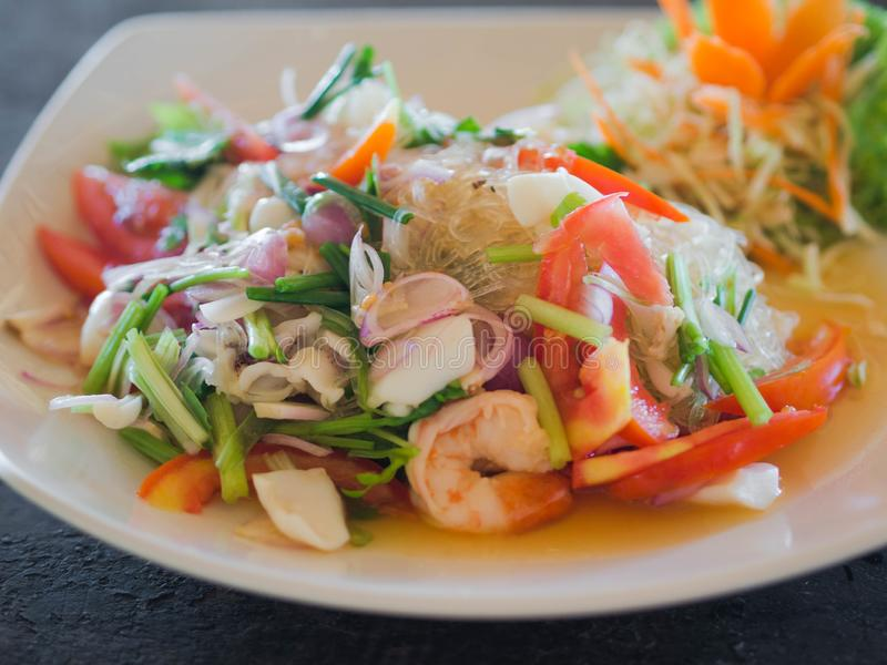 Traditional Thai cuisine. Rice noodle salad, fresh vegetables and herbs and seafood on a plate in a cafe. Authentic fresh. Traditional thai meal at the royalty free stock photography