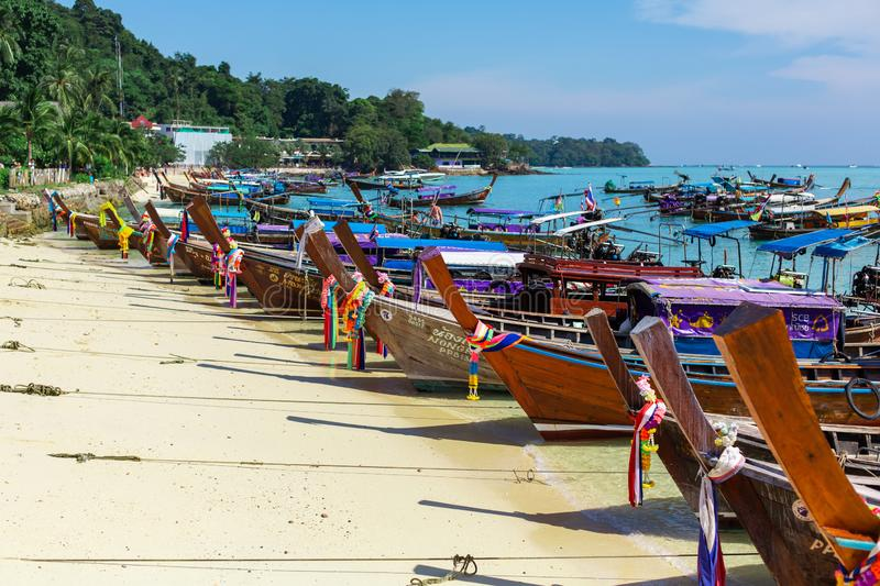 Traditional Thai fishing wooden boats wrapped with colored ribbons. At sand coast of tropical island royalty free stock photos