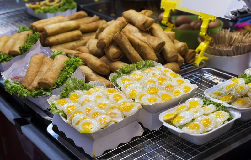 Traditional thai food, fried quail eggs and spring rolls in the street of Thailand.  royalty free stock images