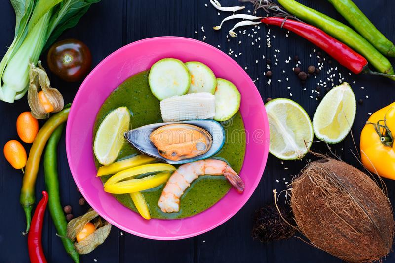 Traditional thai green curry with vegetables, lime, squid, prawn. S and mussel, served in bright plate, decorated with coconut, rambutan, chili peppers,sesame stock images