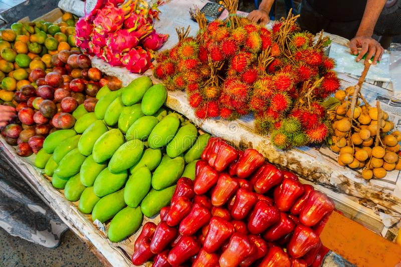 A traditional Thai market stall selling apples and other tropical fruits royalty free stock image
