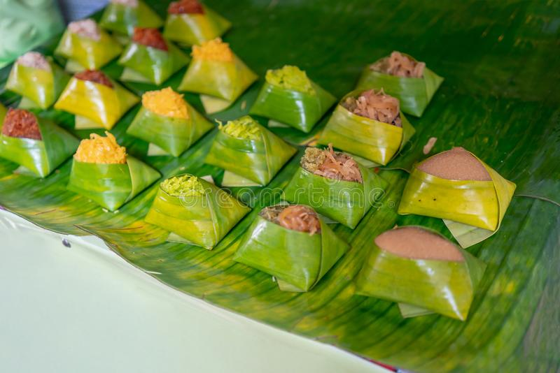 Traditional Thai sticky rice dessert with variety toppings wrapped in banana leaf. stock images