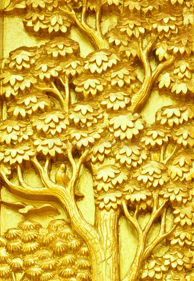 Traditional Thai style art golden tree carving on temple door. Traditional Thai style art golden tree carving on public temple door royalty free stock photography