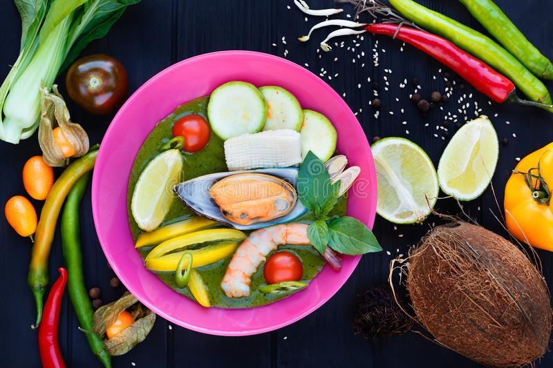 Traditional thai tom yam soup with vegetables, lime, squid, shri. Mp and mussel, served in bright plate, decorated with physalis, coconut, rambutan, chili royalty free stock photos