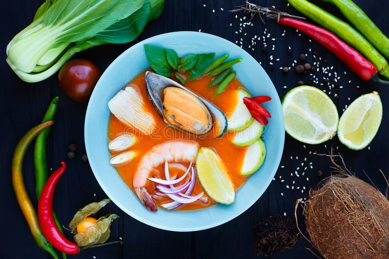 Traditional thai tom yam soup with vegetables, lime, squid, shri. Mp and mussel, served in bright plate, decorated with physalis, coconut, rambutan, chili royalty free stock images
