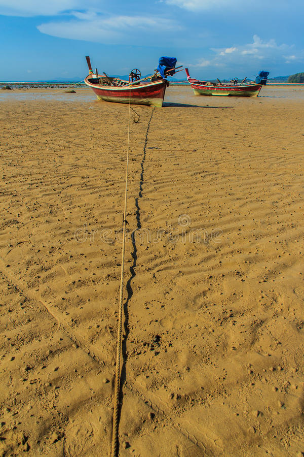 Traditional Thai wooden longtail boats (Rua Hang Yao) moored on. The sand at small pier with blue sky and small island background in Phuket, Thailand stock photos