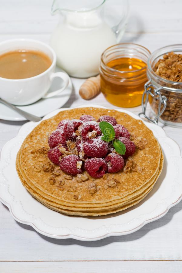 Traditional thin pancakes with fresh raspberries for breakfast. On wooden table, top view royalty free stock photo