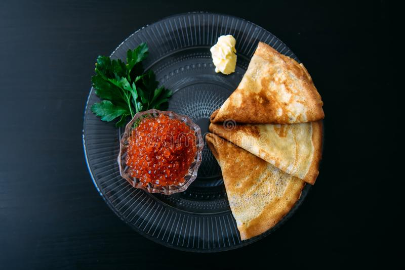 Traditional thin Russian pancakes with red caviar, butter and greens on a black wooden background royalty free stock photos