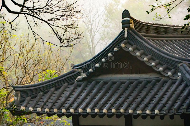 A traditional Chinese roof set against a misty morning background stock photo