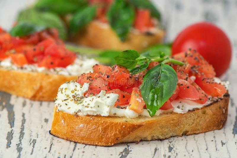 Traditional toasted Italian tomato bruschetta with spice and basil on on light wooden background. Close up royalty free stock photography