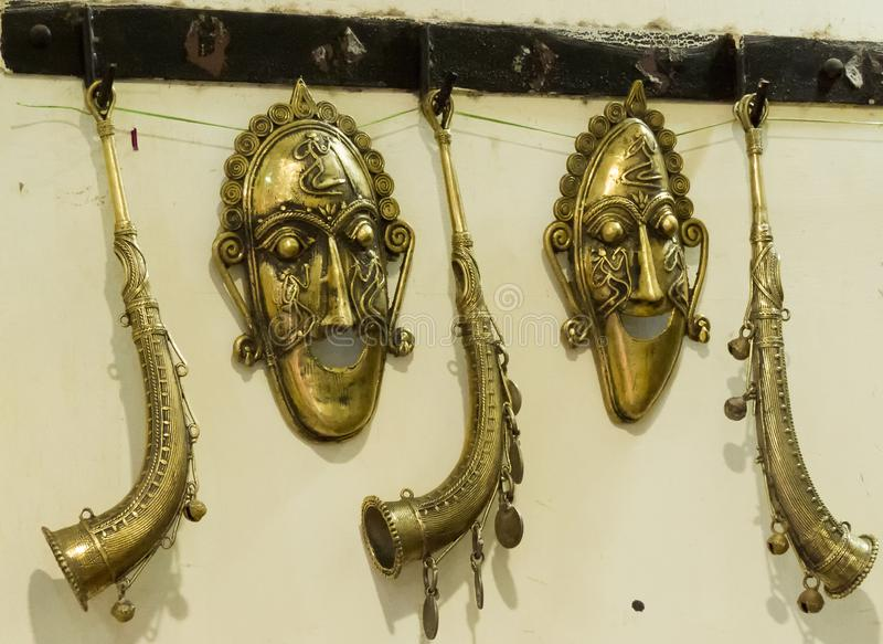 Mask & Bugle made of brass metal handcrafted. Traditional tribal mask of brass metal created by handicraft artist. These kinds of mask mostly used by tribal stock photography