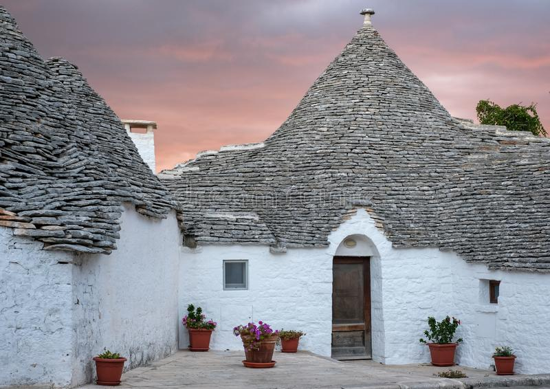 Traditional trulli houses on street in the Aia Piccola area of Alberobello. Photographed early morning with red sky. Alberobello, Puglia, Italy. Traditional dry royalty free stock images