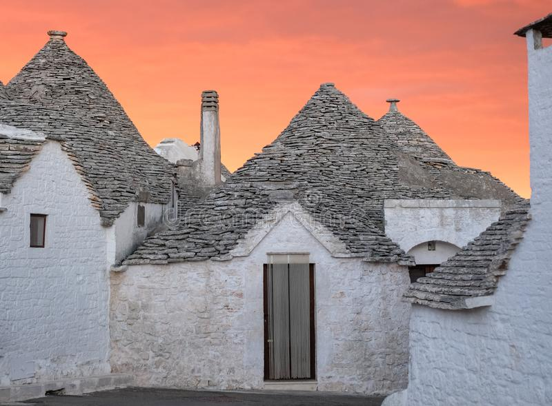 Traditional trulli houses on street in the Aia Piccola area of Alberobello. Photographed early morning with red sky. Alberobello, Puglia, Italy. Traditional dry royalty free stock image