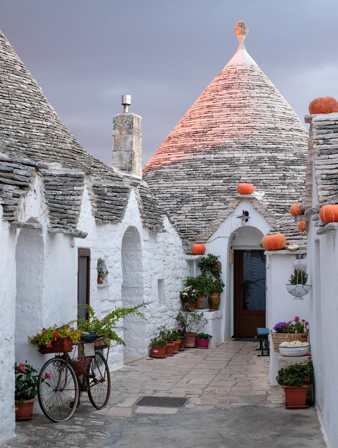 Traditional trulli houses on street in the Aia Piccola area of Alberobello. Photographed early morning with red sky. Alberobello, Puglia, Italy. Traditional dry stock photography