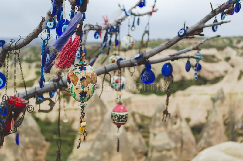 Traditional Turkish amulets and decorations hang on the branches of a wishes tree against the backdrop of the volcanic landscape. Traditional Turkish amulets and stock images