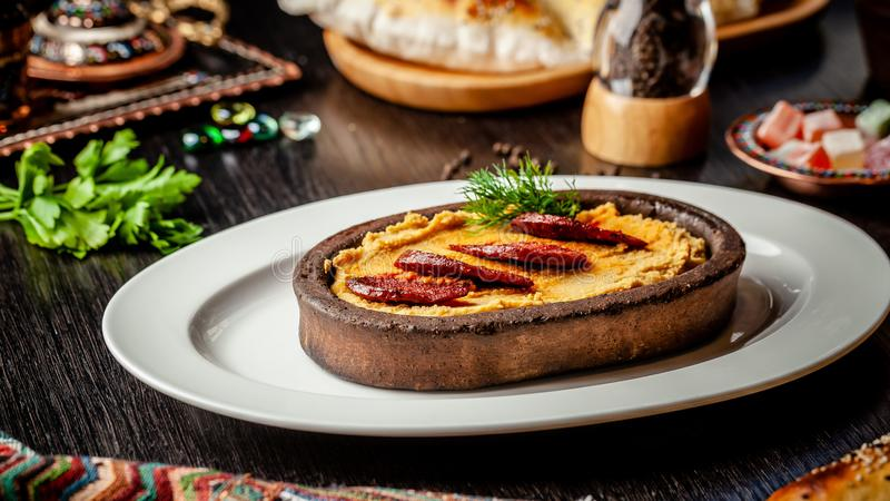 Traditional Turkish, Arabic cuisine. Hummus with salami sausage, in a clay plate, on a wood table. On a white plate royalty free stock photo