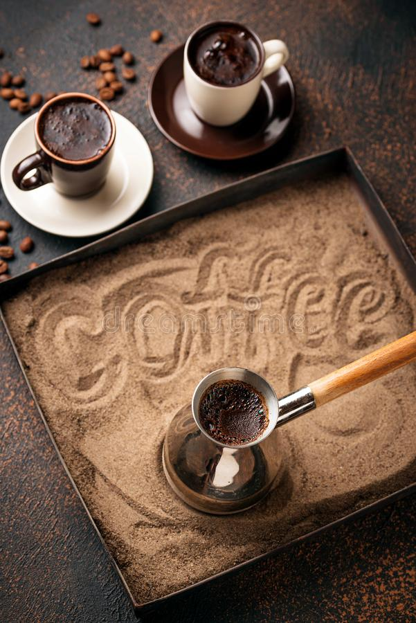 Traditional turkish coffee prepared on hot sand. Traditional turkish coffee in cezve prepared on hot sand. Selective focus, toned royalty free stock photos