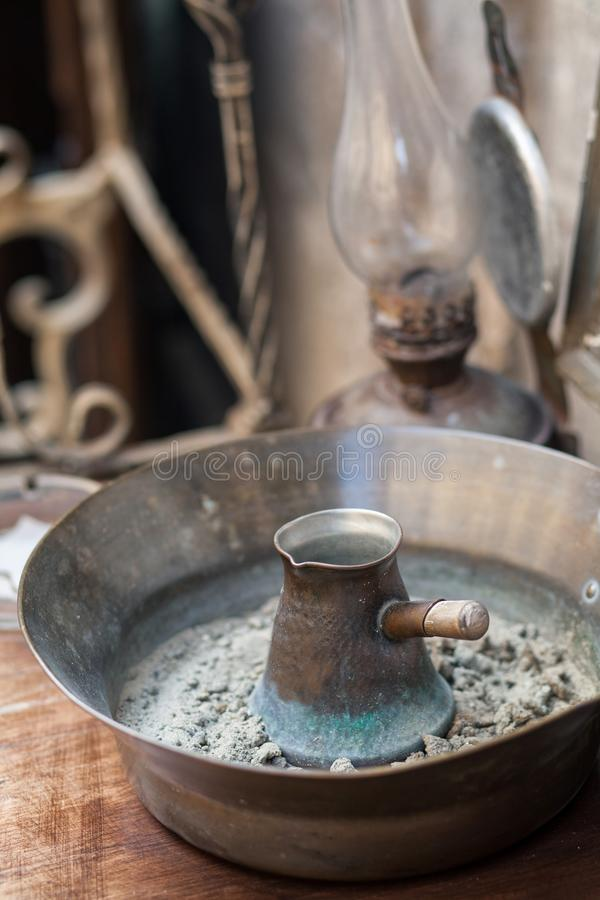 Traditional turkish coffee in cezve prepared on hot sand. Selective focus royalty free stock images