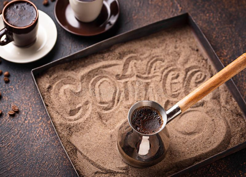 Traditional turkish coffee prepared on hot sand. Traditional turkish coffee in cezve prepared on hot sand. Selective focus royalty free stock photography