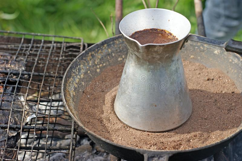 Turkish coffee in cezve prepared on a pan with hot sand. Traditional turkish coffee in cezve prepared on a pan with hot sand burning coals stock photo