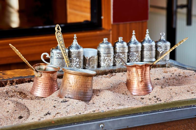 Traditional Turkish coffee cooked in hot sand and three copper coffee pot stock images