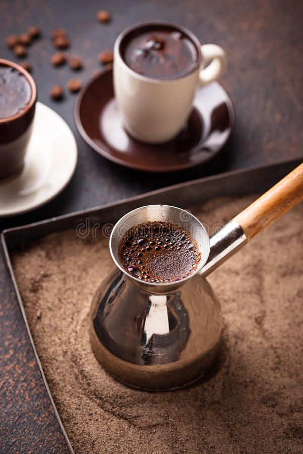 Traditional turkish coffee prepared on hot sand. Traditional turkish coffee in cezve prepared on hot sand. Selective focus royalty free stock image