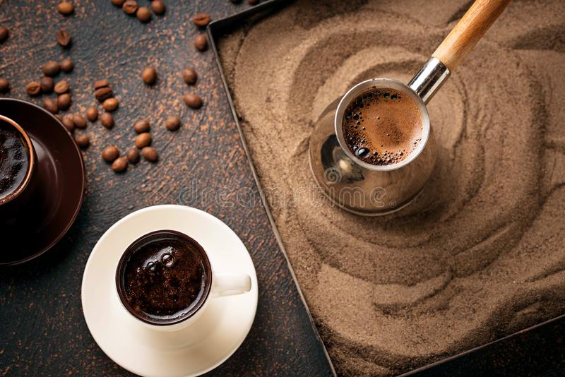 Traditional turkish coffee prepared on hot sand. Traditional turkish coffee in cezve prepared on hot sand. Selective focus stock photos