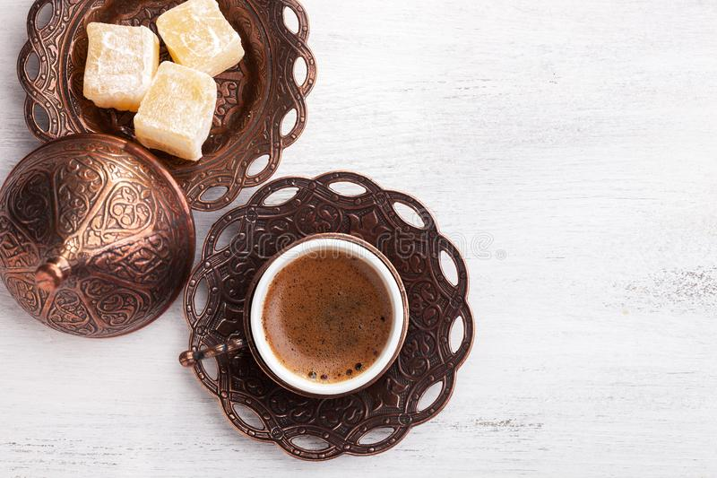 Traditional turkish coffee and turkish delight on white shabby wooden background. flat lay royalty free stock image