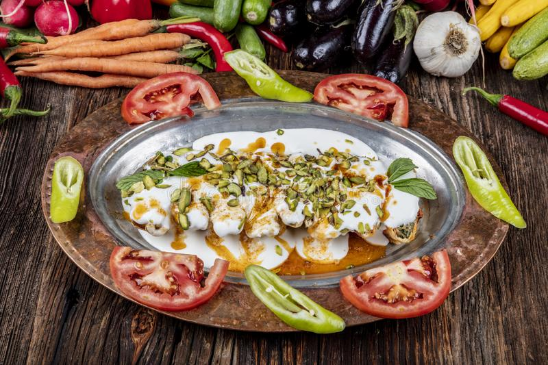 Turkish Beyti kebab served with grilled vegetables and yoghurt sauce on rustic wooden table royalty free stock photos