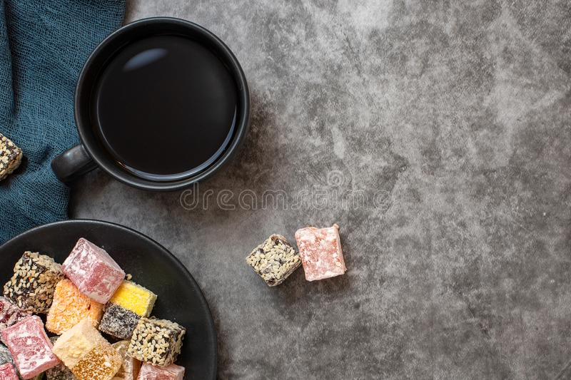Traditional turkish delight and cup of coffee on grey background. Flat lay. With copy space royalty free stock images
