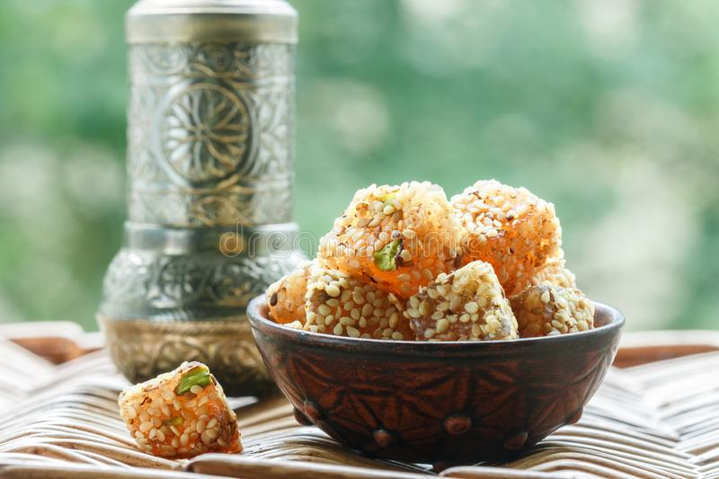 Traditional Turkish delight. lokum. Oriental sweets with sesame and pistachios. In a ceramic bowl on the table. A treat for tea. Selective focus, copy space stock photography