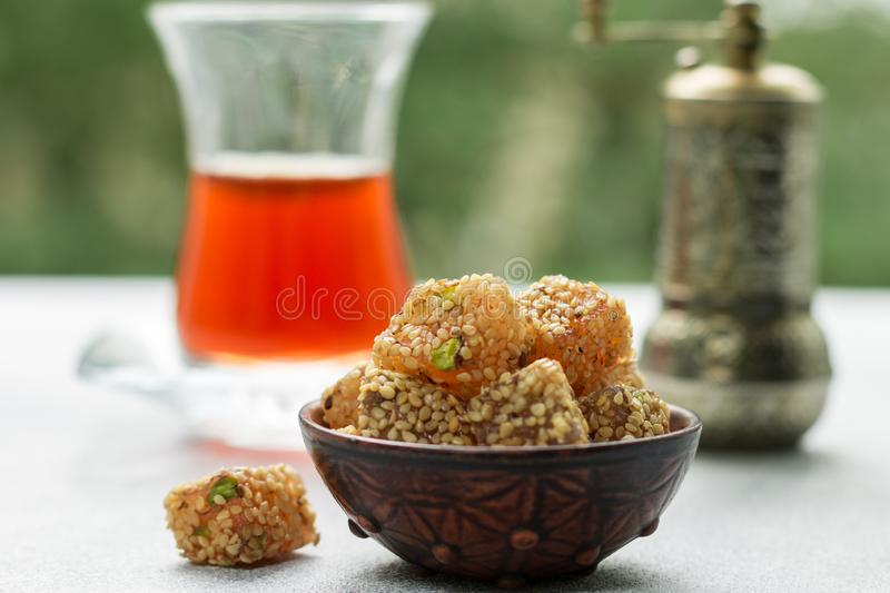 Traditional Turkish delight. lokum. Oriental sweets with sesame and pistachios. In a ceramic bowl on the table. A treat for tea. Selective focus, copy space stock photos