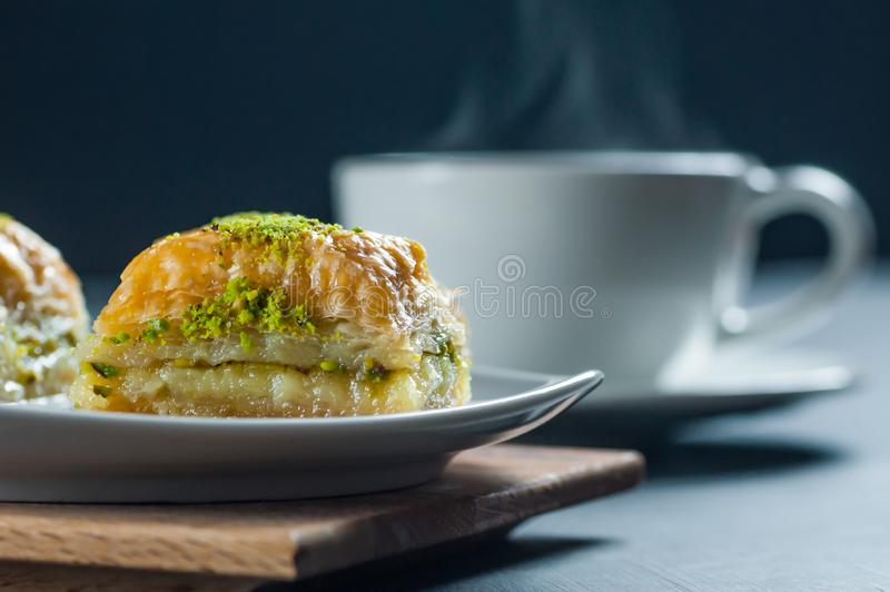 Traditional turkish dessert antep baklava with pistachio on white plate on burlap sack royalty free stock images
