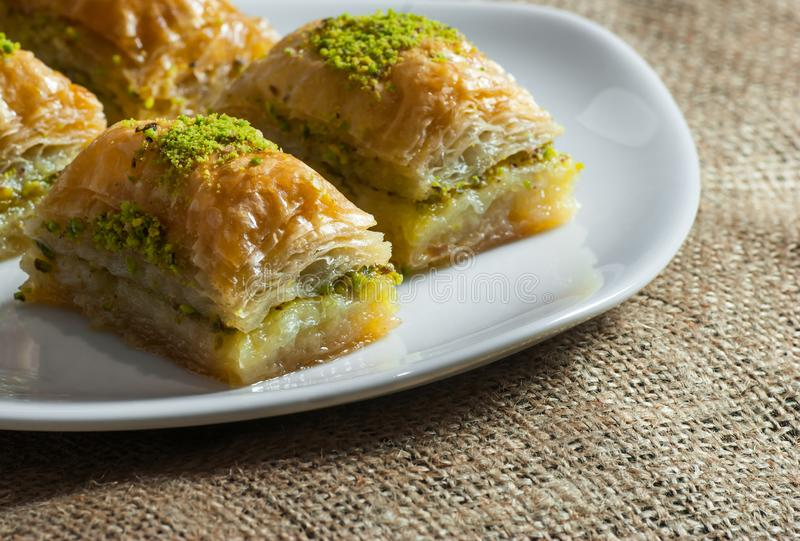 Traditional turkish dessert antep baklava with pistachio on white plate on burlap sack. Desserts concept royalty free stock photos