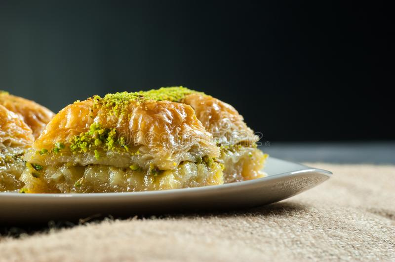 Traditional turkish dessert antep baklava with pistachio on white plate on burlap sack. Desserts concept stock images