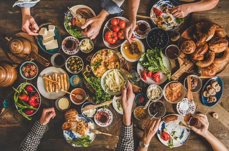 Traditional Turkish family breakfast table and people taking various food. Turkish breakfast table. Flat-lay of peoples hands taking pastries, vegetables, greens royalty free stock image