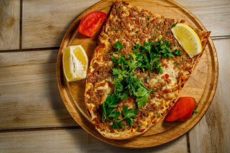 Traditional Turkish food Lahmajun on a wooden tray. stock photography