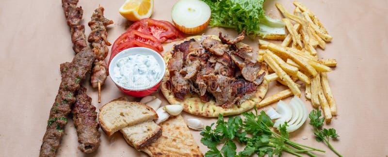 Traditional turkish, greek meat food. Shawarma, gyros, kebab, souvlaki and tzatziki on pita bread royalty free stock image